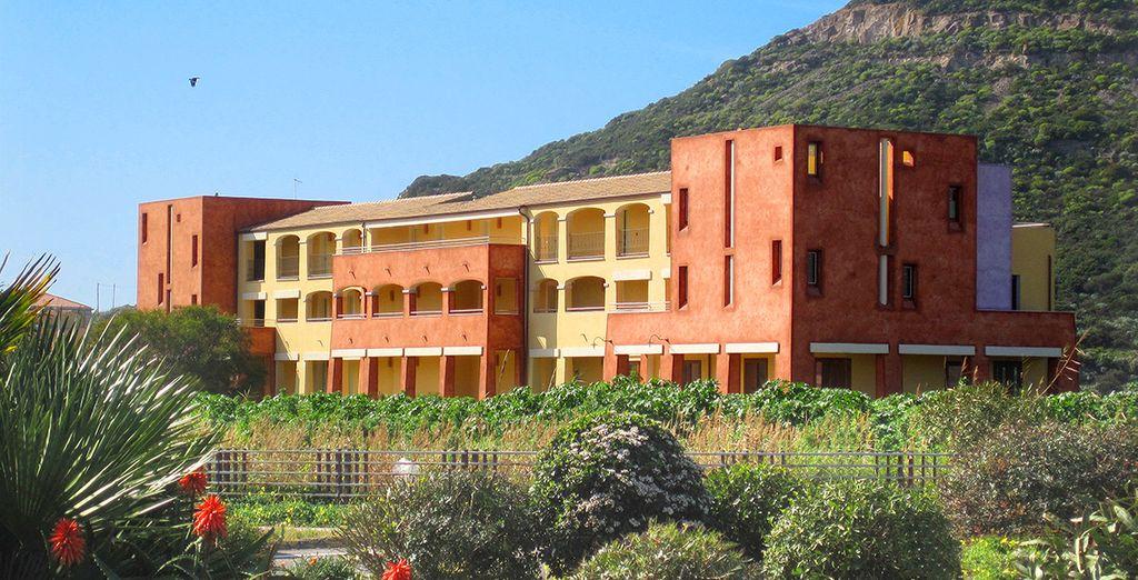 El edificio del hotel de estilo mediterráneo está rodeado por un gran jardín que bordea el paseo marítimo de la marina