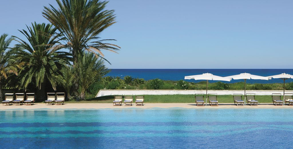 Dive right into the expansive pool backed by the sea